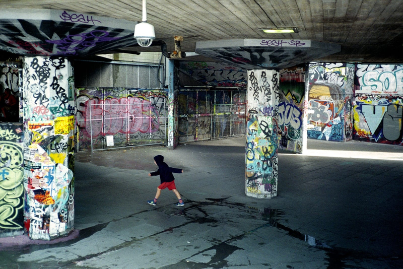Photograph of a child walking past graffiti covered walls