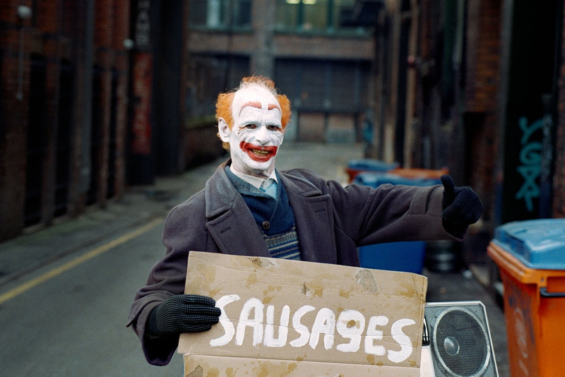 Photograph of a clown holding a sign with the word sausages painted in white