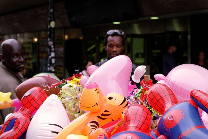 Photograph of colourful inflatable toys with two men in the background